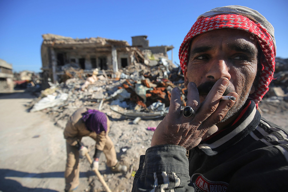 עובדים מנקים הריסות רחוב בעיר העתיקה במוסול, לשעבר בירת דאעש בעיראק (צילום: AFP)