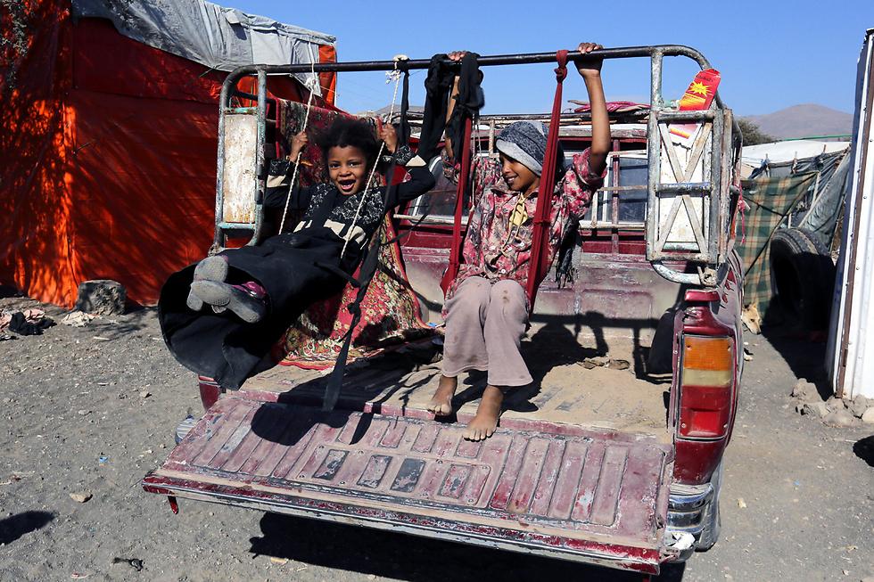 ילדות מתנדנדות בנדנדות מאולתרות על רכב במחנה עקורים בעמראן, תימן (צילום: EPA)