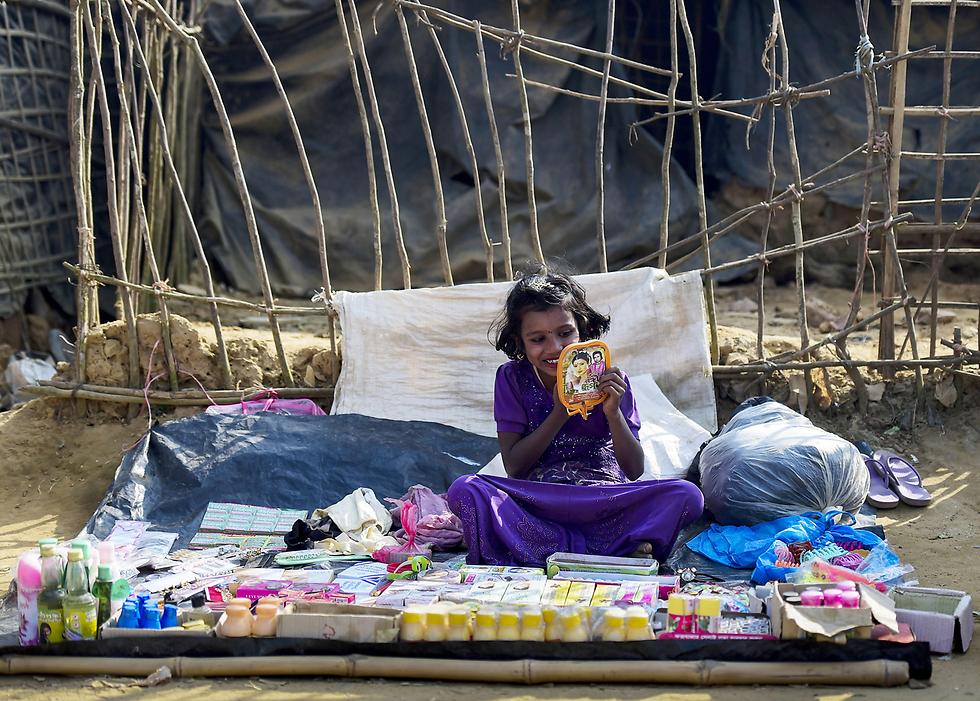 פליטה בת רוהינגה בדוכן לממכר מוצרים שונים במחנה פליטים בבנגלדש (צילום: AFP)