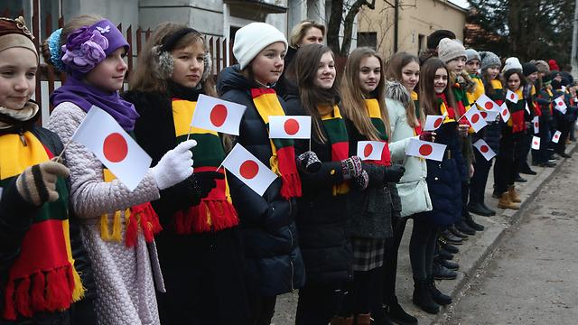 ילדים ליטאים מקבלים את פני שינזו אבה (צילום: AFP) (צילום: AFP)