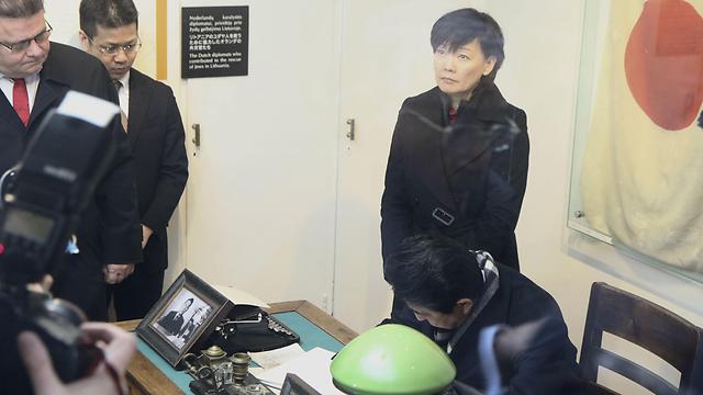 ראש ממשלת יפן חותם בספר המבקרים על השולחן ששימש את סוגיהרה (צילום: AFP) (צילום: AFP)