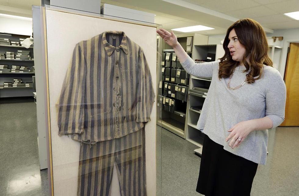 Shoshana Greenwald talks about the 1945 uniform of Bergen-Belsen concentration camp survivor Chaim Schmidt, in the museum's archive room (Photo: AP)