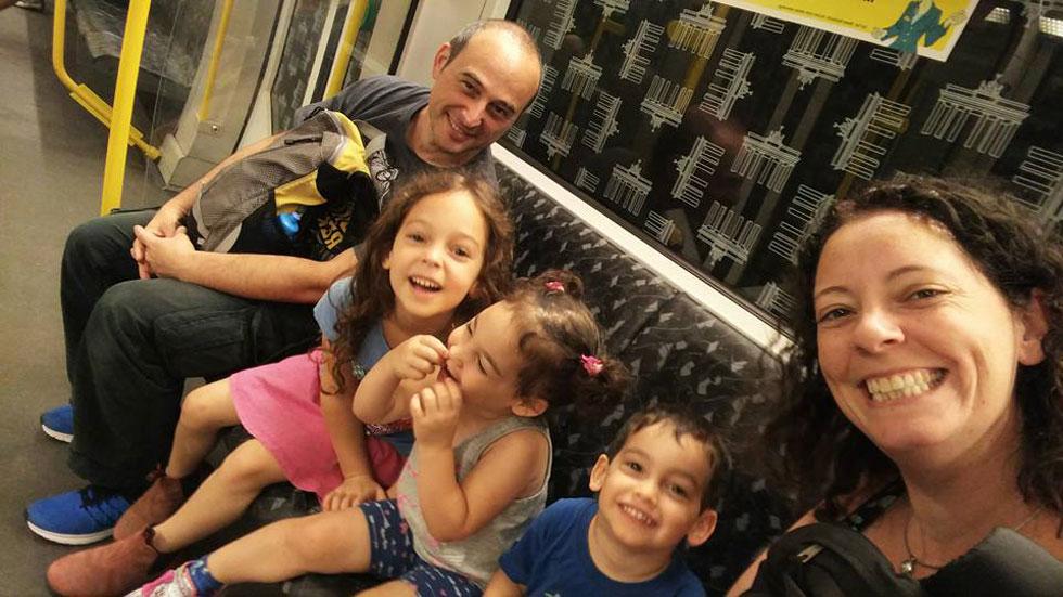 """טליה, רוני ושלושת הילדים ברכבת התחתית בברלין. """"אנחנו מקפידים לטוס בשעות היום, כדי שלא נצטרך לקום עם הילדים באמצע הלילה""""   (צילום: טליה קליין פרז)"""