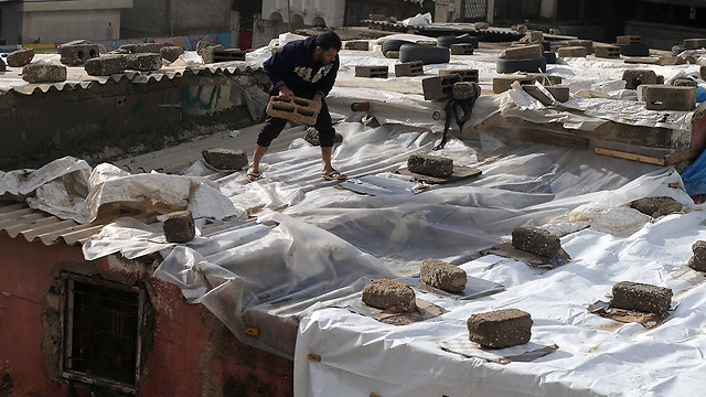 Residents covering their homes' roofs with nylon sheets (Photo: AFP)