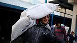 Man carries UNRWA flour sacks in Gaza
