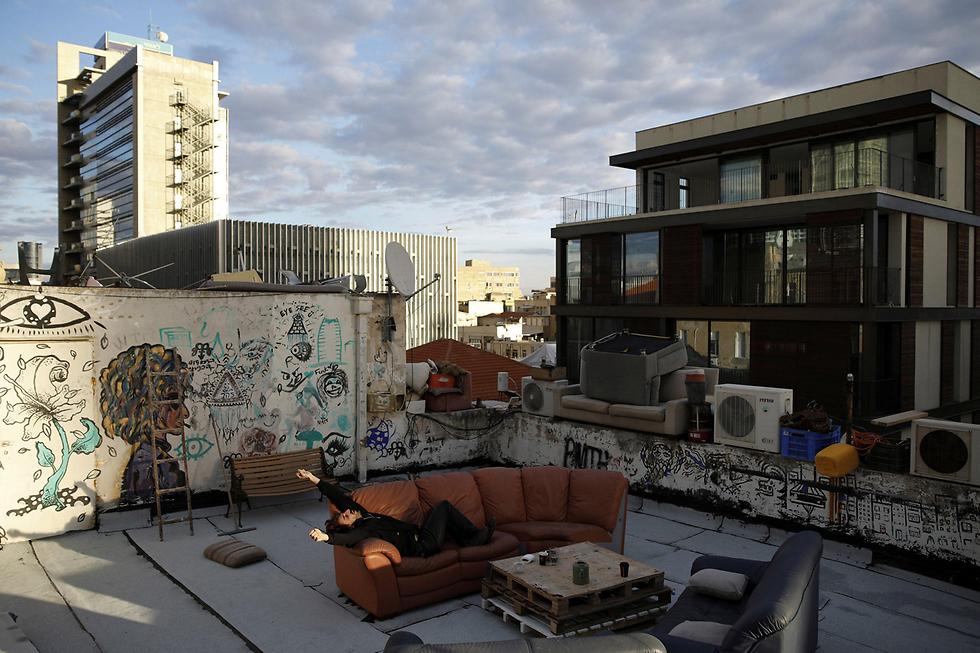 """גיא אלחדד (26) שוכב על ספה על גג ביתו בתל-אביב. עבור גיא הגג הוא חממת יצירה: """"בו אנחנו יכולים לעשות מה שאנחנו רוצים כי אנחנו לא צריכים אישור מאף אחד אחר"""". הוא ושותפיו מארחים שיעורי יוגה, מוזיקה ואומנות, ובנו גם חדר שינה נוסף לאנשים שמתארחים אצלם (צילום: רויטרס) (צילום: רויטרס)"""