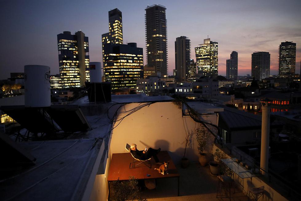 אלכסנדר פלשנברג (60) יושב על כיסא המונח על שולחן כדי ליהנות מנוף הים על גג ביתו בתל-אביב. הגג הזה הוא גן עדן פרטי לאלכסנדר, ונותן לו הזדמנות להירגע מהעבודה (צילום: רויטרס) (צילום: רויטרס)