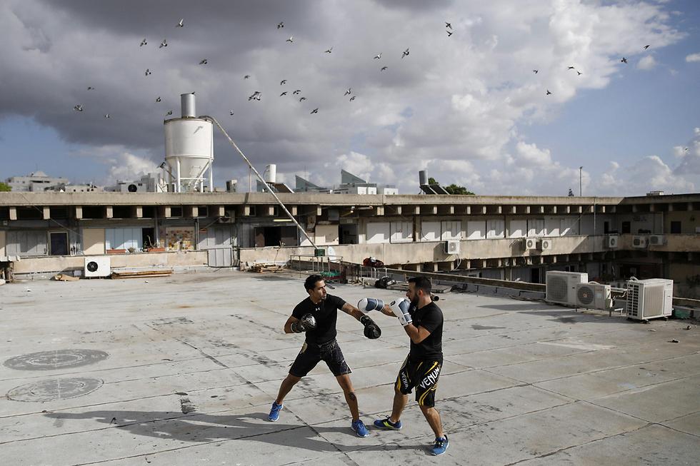 מדריכי הקרב-מגע דורון תורג'מן (35) ומיכאל אלימלך (26) מתאמנים על גג בניין בגבעתיים שבו הם מעבירים קורסים (צילום: רויטרס) (צילום: רויטרס)