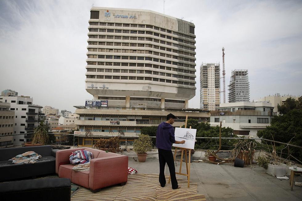הצייר החובב קובי מלול (31) מצייר על גג ביתו בתל-אביב (צילום: רויטרס) (צילום: רויטרס)