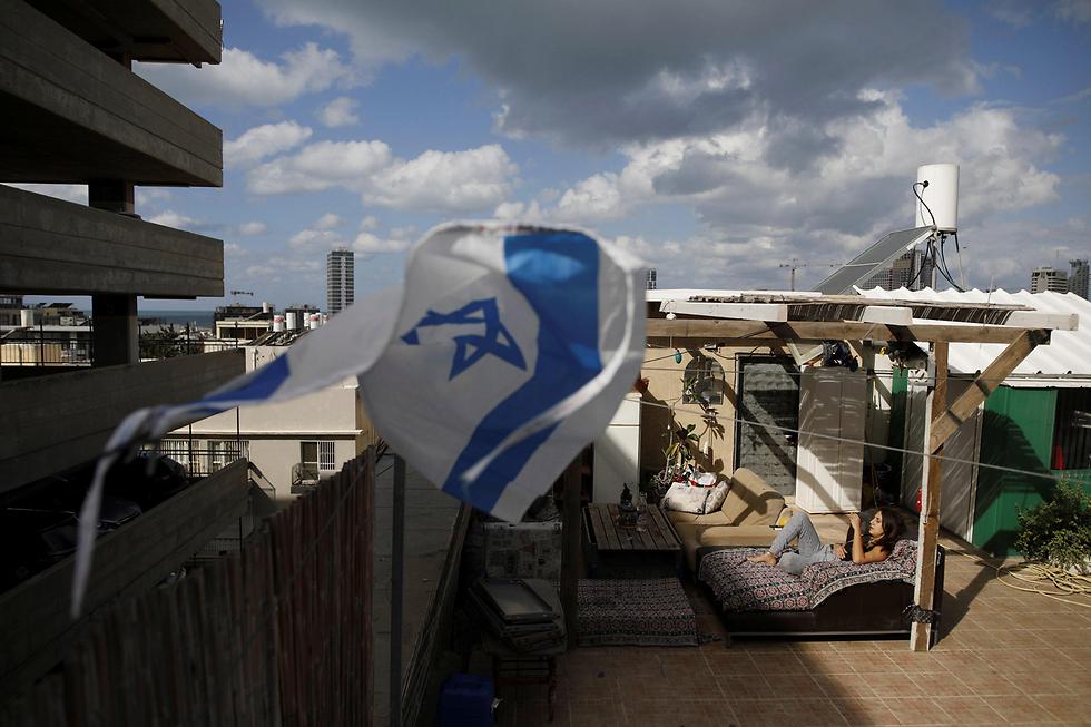 מעיין סעדי (28) מעשנת סיגריה על גג ביתה, ליד חניון רב קומות בתל-אביב (צילום: רויטרס) (צילום: רויטרס)