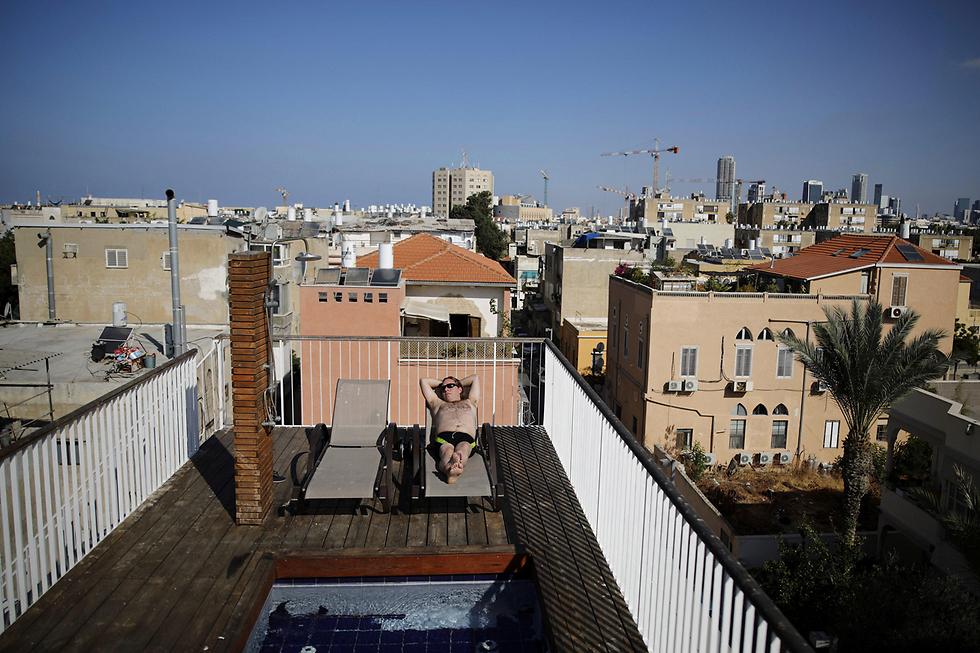 אביה מורג (25) תופס שמש על גג ביתו, המצויד בבריכה קטנה, מקלחת וכיסאות עץ (צילום: רויטרס) (צילום: רויטרס)