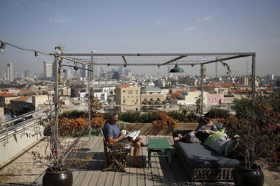 מוני חורב (60) וגילי חורב (59) יושבים על גג ביתם - שגילי תכננה ועיצבה בעזרת מעצב מקצועי (צילום: רויטרס) (צילום: רויטרס)