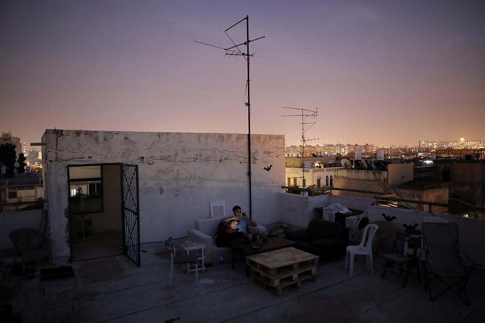 """חנה ווימברלי (26) ועמנואל כהן (36) מבלים על גג ביתם בתל-אביב. חנה הפכה את גג הבטון השומם לגן עדן פרטי בעזרת כמה כיסאות, ספה ושולחן עץ: """"יותר מהכול - זה מקום שמאפשר לי להרגיש מחוברת לעיר. תל-אביב, עם כל זה שיש בה הרבה מה לעשות ואפשר ללכת בה לפאב ולבזבז 50 שקל על שתייה, נעשית מתישה"""" (צילום: רויטרס) (צילום: רויטרס)"""