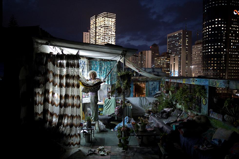 """אנה אשורי לצד יצירות האומנות שלה על גג ביתה ברמת גן. העיר מוצגת בפרויקט כ""""פרבר של תל-אביב"""" (צילום: רויטרס) (צילום: רויטרס)"""