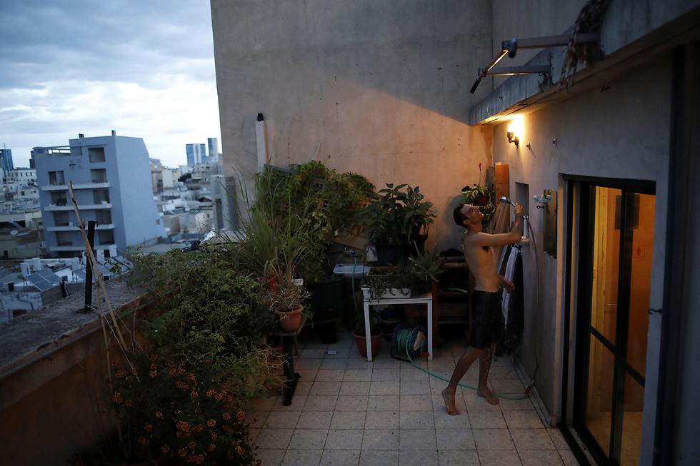 עמנואל כהן (36) מתקלח על גג ביתו. הוא משתמש בגג כגן קטן לגידול צמחים וירקות, וכשמזג האוויר מאפשר זאת - הוא אוהב להתקלח שם (צילום: רויטרס) (צילום: רויטרס)
