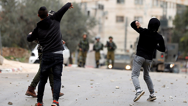 Palestinians hurling stones at IDF troops early Thursday (Photo: Reuters)