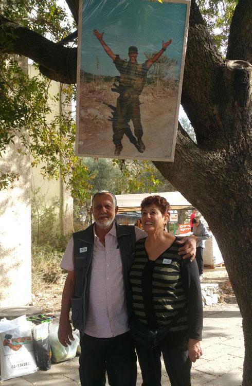 """ההורים טליה ודוד שרביט בברקאי, תחת תמונת בנם רתם ז""""ל. חיפשו פרויקט הנצחה שיהלום את אופיו ודרכו  (צילום: מירי בלבול)"""