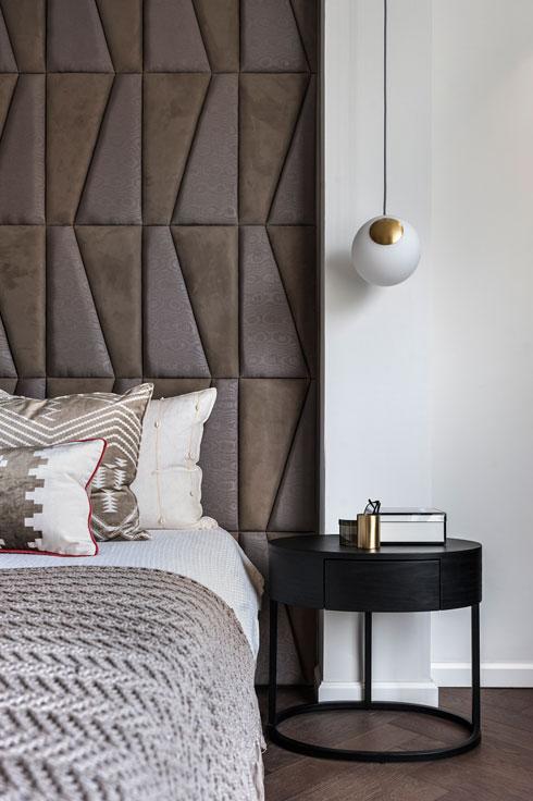 גב המיטה גבוה ומרופד ולצדו תלויה מנורה מזכוכית ופליז (צילום: עודד סמדר)