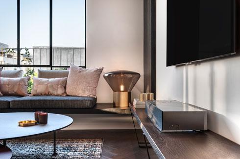 שולחנות הסלון העגולים, הכריות על הספסל וגופי התאורה מרככים את הנוקשות של הצורות הגיאומטריות (צילום: עודד סמדר)