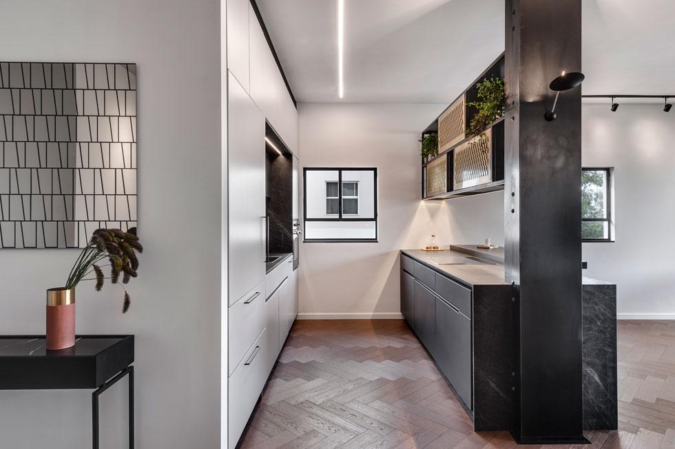 משמאל: מראה חרוצה בדוגמת טרפזים, מעל קונסולת ברזל צרה בכניסה. המטבח בנוי כשני פסים מקבילים, והאי נמתח בין הקיר לעמוד תמך שחודר לתוכו, ונעטף בברזל. האי כוסה באבן שחורה מוברשת (צילום: עודד סמדר)