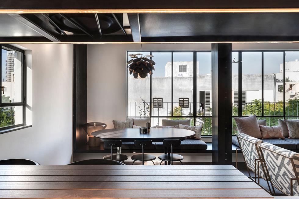 שולחן האוכל האליפטי יכול להיפתח עבור 12 סועדים ומעליו תלויה מנורת עלים של Marset. בדירה בולטים פריטים של חברות עיצוב נורדיות (צילום: עודד סמדר)
