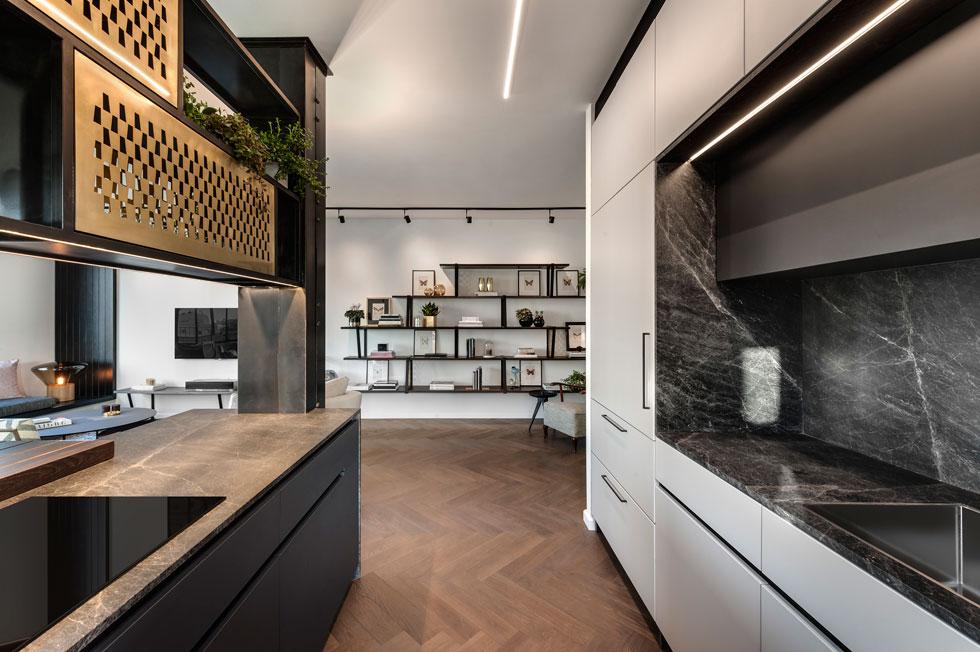 בקיר ארונות המטבח הגבוהים נפערה נישה למשטח עבודה עטוף במשטחי אבן שחורה, ובתוכה כיור וארון קלפה עליון (צילום: עודד סמדר)