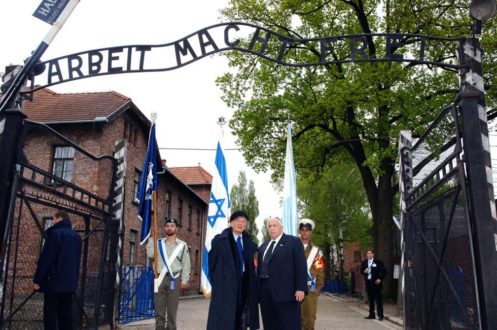 """באושוויץ, עם ראש הממשלה אריאל שרון, 2005. מה הוא היה אומר על החוק שמאפשר גירוש וכליאה של מבקשי מקלט? (צילום: אבי אוחיון, לע""""מ)"""
