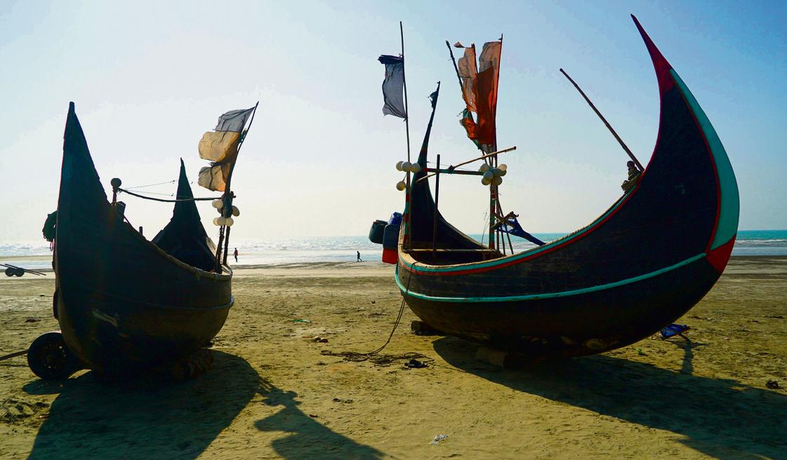 סירות הדייגים הבנגליות (מימין) ודייג בחוף  קוקס־בזאר. יותר  מחצי מיליון רוהינגה  חצו בחודשים האחרונים  את המצר