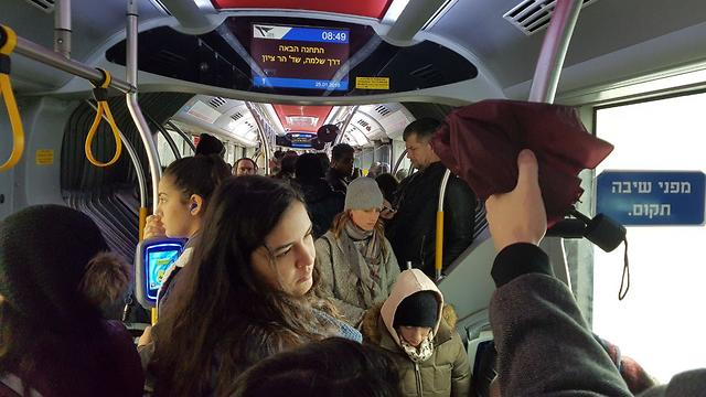 Passengers forced to stand on packed buses delayed in floods (Photo: Asaf Zagrizak)