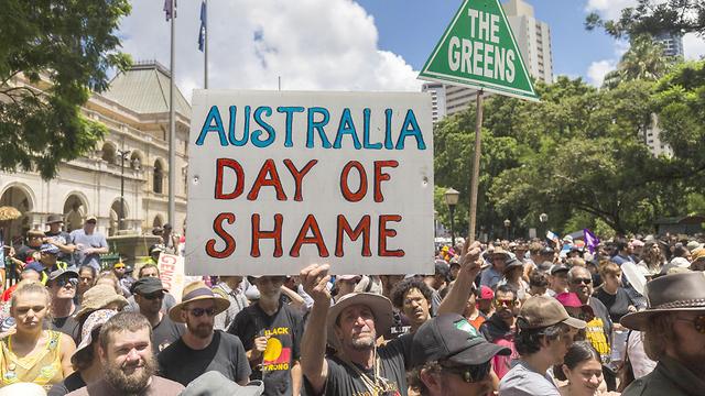 """מפגינים בבריזבן מניפים את השלט """"יום הבושה של אוסטרליה"""" (צילום: EPA) (צילום: EPA)"""