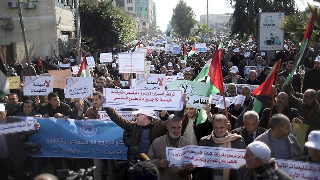 """הפגנה נגד הקיצוץ האמריקני בתקציב אונר""""א (צילום: AP) (צילום: AP)"""