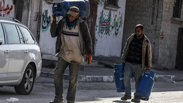 Men in Gaza carrying water home for lack of running water (Photo: AFP)