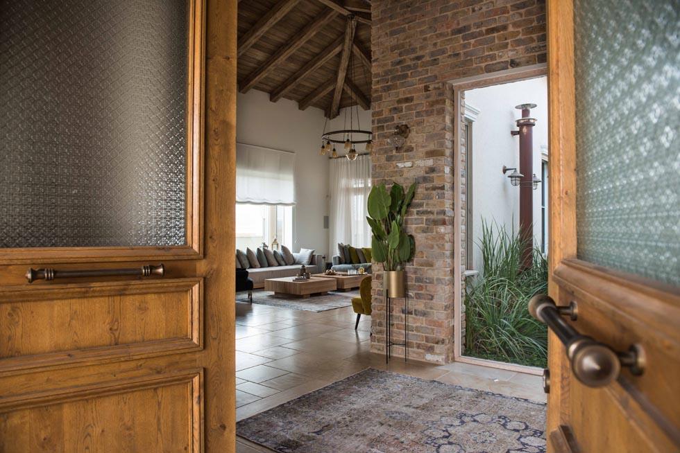 הדלת נפתחת אל מול הפטיו הירוק שמפריד בין שני אגפי הבית. משמאל הסלון, עם תקרת עץ משופעת ובעלת נוכחות מודגשת (צילום: גלעד רדט)