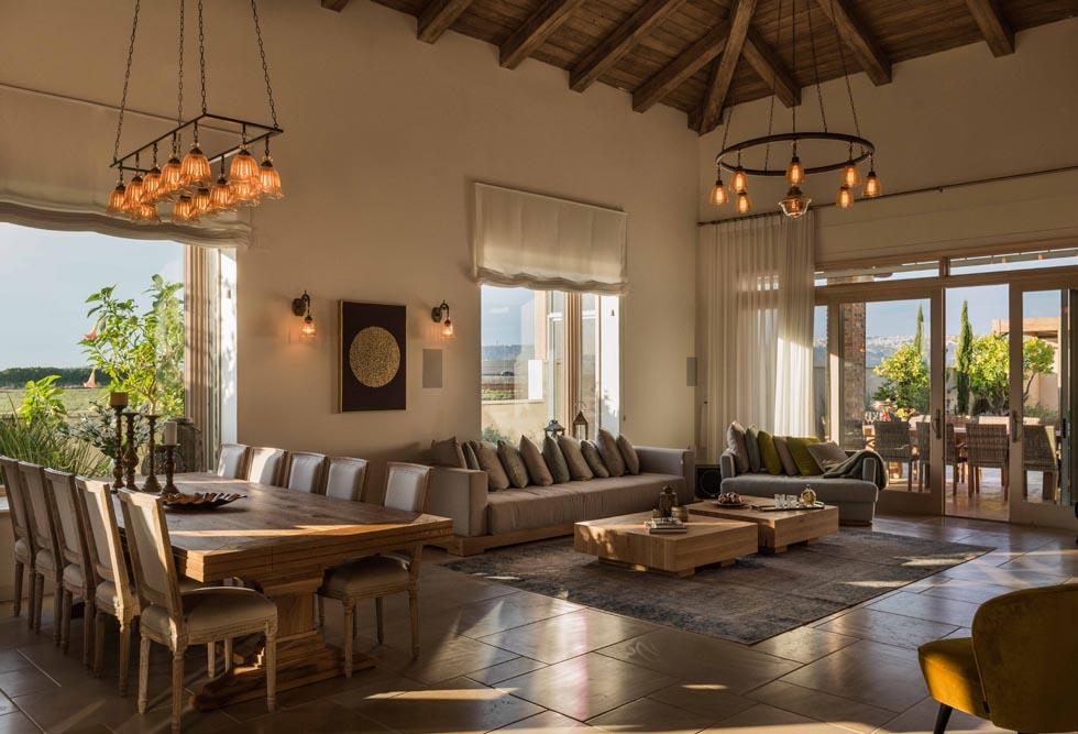 הסלון ופינת האוכל. הבית מרוצף באריחי אבן בעיבוד כמו-עתיק. החלונות הגדולים מכניסים לתוכו את הנוף  (צילום: גלעד רדט)