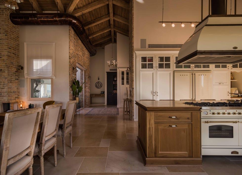 מבט מכיוון המטבח אל מבואת הכניסה והאגף הפרטי של הבית. ארונות המטבח עוצבו עם דלתות זכוכית סבתא וקרניזים. מעל האי קולט אדים גדול שיוצר בהזמנה מיוחדת, ותעלת מיזוג האוויר (למעלה משמאל) עשויה מנחושת (צילום: גלעד רדט)