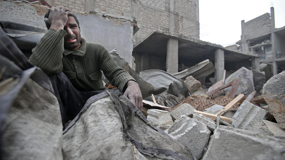 A Syrian man mourns over his destroyed home in Arbin in the eastern Ghouta region (Photo: AFP)