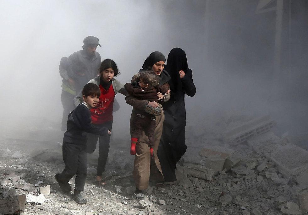 אזרחים מנסים לתפוס מחסה מההפצצות בפרברי דמשק (צילום: AFP)