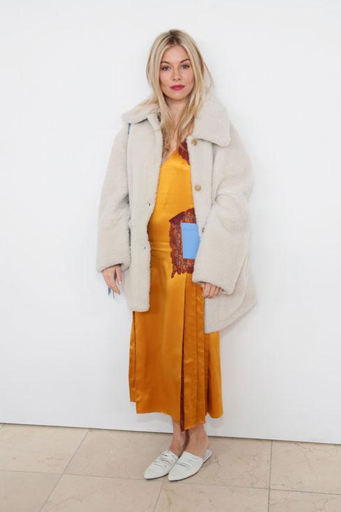 מעיל גדול, שמלת סאטן יפה ובליטה קטנה באזור הבטן. סיינה מילר בתצוגה של טורי בורץ' (צילום: Gettyimages)