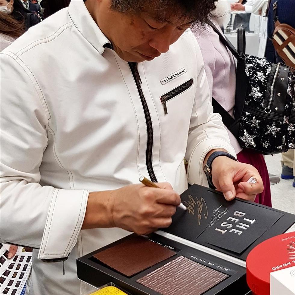 הכוכב היפני, אי קויאמה, חותם על מארזי שוקולד (צילום: איקה כהן) (צילום: איקה כהן)