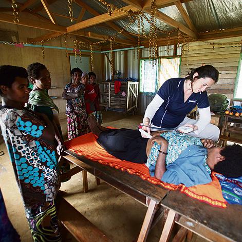 המיילדת  ליהי עמיצור לובל בודקת יילוד  ואישה הרה בכפר באנגוואט