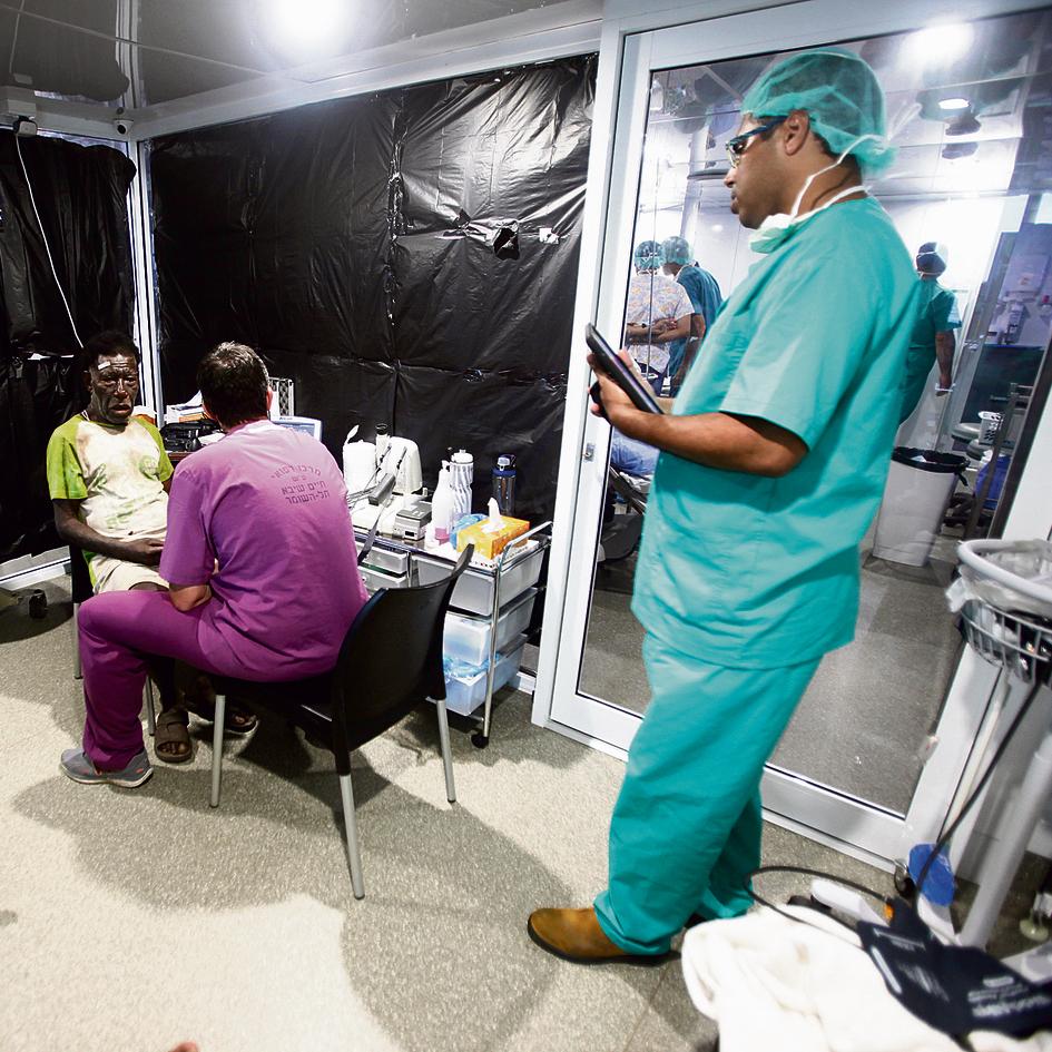 """מנתח העיניים  ד""""ר אלון סקעת (מימין) והאח חן פסטרנק בודקים מטופל לאחר  ניתוח עיניים"""