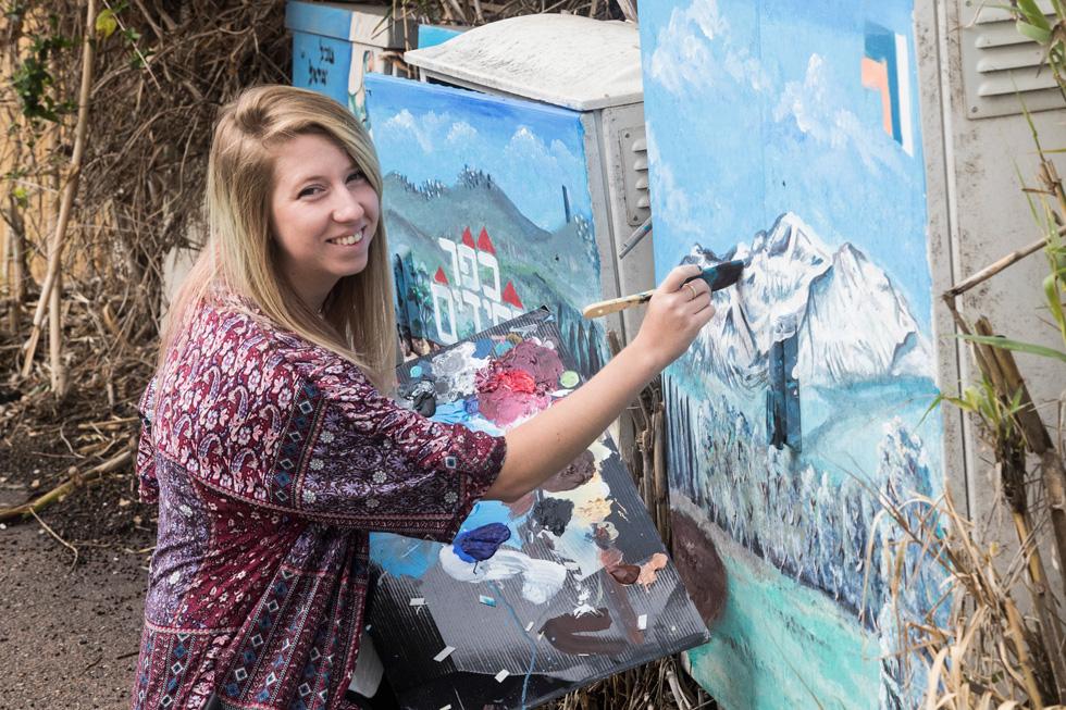 """מציירת על בניין בכפר חסידים. """"אם יש לאדם כישרון כלשהו, הוא יוכל להיעזר בו בכל מקום"""" (צילום: גיל נחושתן)"""