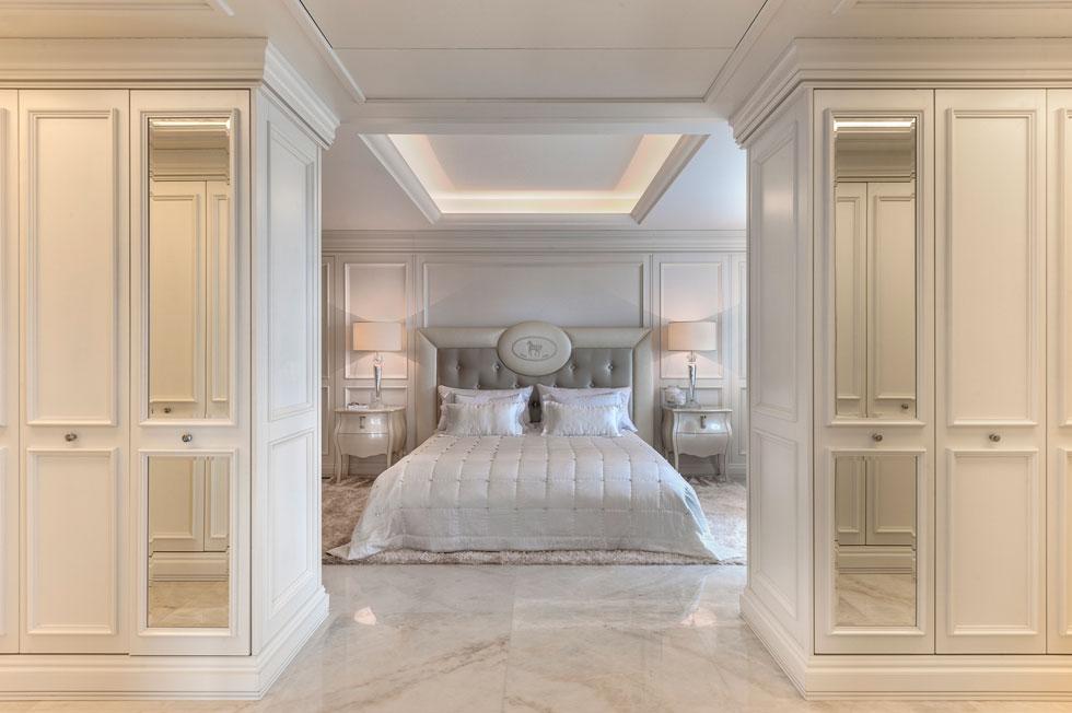 כיסוי המיטה משובץ באבני סברוסקי ועל הרצפה שטיח רך מחוטי משי. החדר הגדול חולק באמצעות קירות נגרות לשלושה חלקים סימטריים: בתמונה מבט מחדר הארונות, שדלתותיו עוטרו בקרניזים המאפיינים את הקירות (צילום: עודד סמדר)