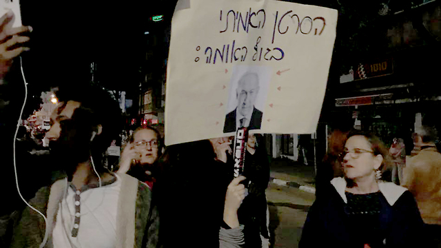 """מפגינים נגד גירוש מבקשי המקלט בת""""א עם שלט מסית נגד ראש הממשלה ()"""