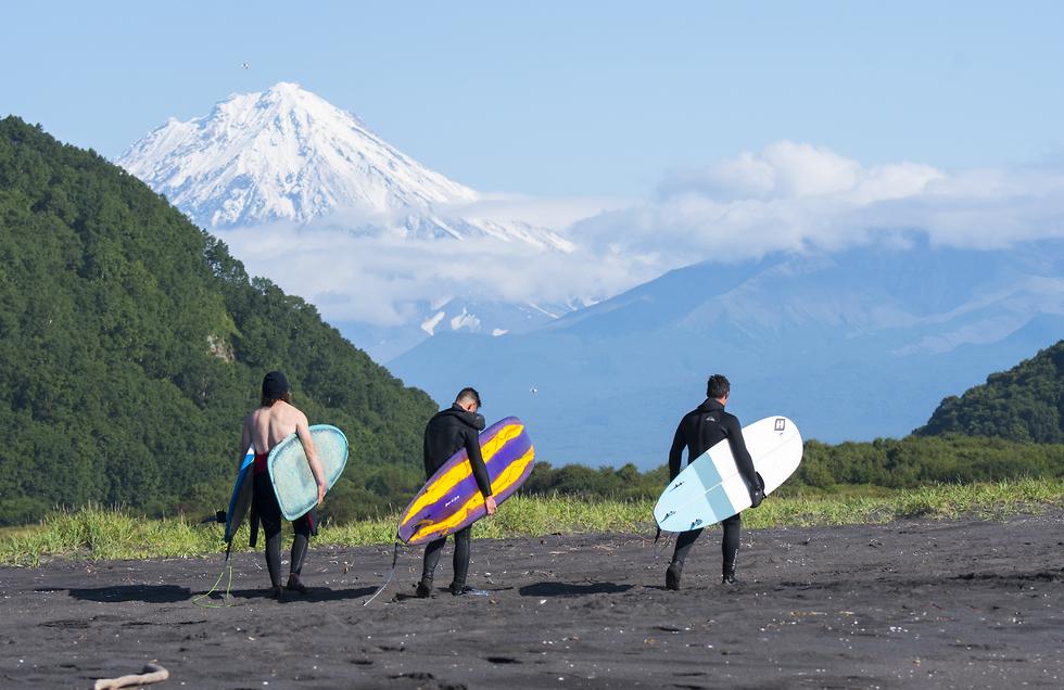 הולכים עם הגלשנים על רקע הר הגעש קוריאקסקי (צילום: אורי מגנוס) (צילום: אורי מגנוס)