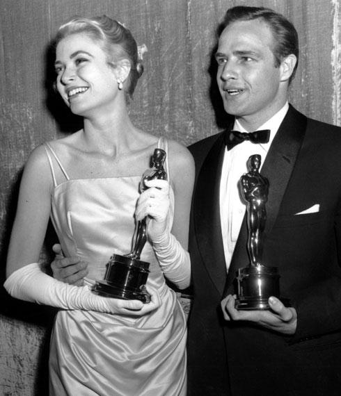 שמלה של אדית הד ופסלון מוזהב. גרייס קלי עם מרלון ברנדו, 1955 (צילום: AP)