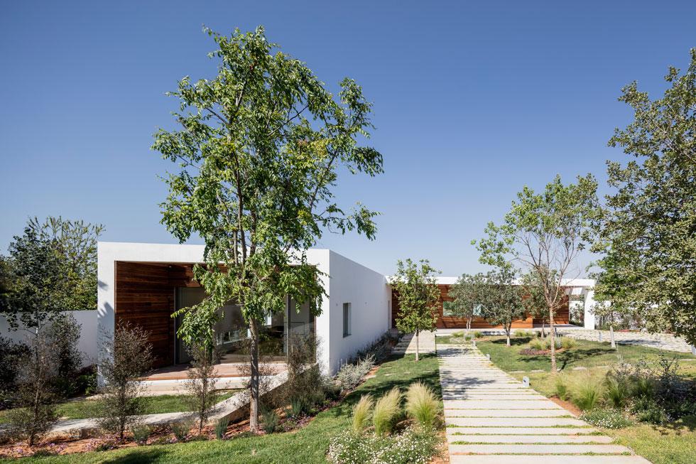 שביל של מדרכי בטון מוביל בין עצי הגן אל דלת הכניסה, ששולבה בחזית עץ אחידה וממוסגרת בלבן. משמאל חדרו של הבן הבוגר (צילום: עמית גרון)