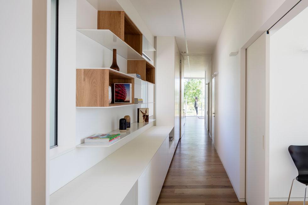 מבט מאזור המטבח אל המסדרון שבסופו חדר ההורים. מימין חדר עבודה עם דלתות הזזה שנאספות לתוך הקיר, ובתווך חדר שינה נוסף (צילום: עמית גרון)