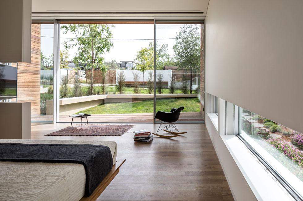 מבט מתוך החדר אל הגינה הקדמית. יש לו מרפסת ממוסגרת ומעין חצר אינטימית שנחפרה לתוך הקרקע, נתמכת בקיר/ספסל נמוך מבטון חשוף (צילום: עמית גרון)