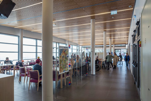 חלל השהייה הגדול, שמשמש את חדר האוכל ופינת הישיבה, עם עמודים עגולים (צילום: ליאור גרונדמן)